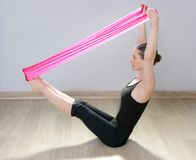Pilates yoga resistance band red rubber gym woman Royalty Free Stock Photo