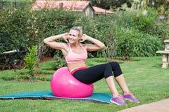 Pilates zu Hause im Garten mit einem Turnhallenball Stockfotografie