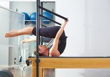 Pilatesvrouw in hervormerbroodje over oefening stock fotografie