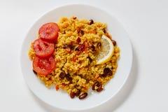 Pilau de Bulgur com feijões, bérberis, paprika, alho, tomate, limão e especiarias no fundo branco Foto de Stock Royalty Free