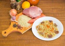 Pilau e ingredientes cozinhados para sua preparação na tabela do cozinheiro Imagem de Stock