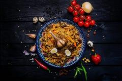 Pilau en ingrediënten op plaat met oosters ornament op een donkere houten achtergrond Centraal-Aziatische keuken - de Hoogste men Stock Foto