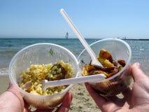Pilau, fatias da batata e veleiro no horizonte no mar Foto de Stock