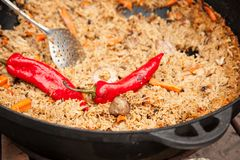 Pilau met vlees en groenten en rode grote die Spaanse peper op ketel op brand met nevel wordt gekookt Straatvoedsel royalty-vrije stock foto