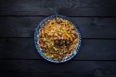 Pilau na placa com ornamento oriental em um fundo de madeira Culinária do Central-asiático - Plov Vista superior Fotografia de Stock Royalty Free
