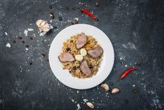 Pilau na placa com ornamento oriental em um fundo escuro Culinária do Central-asiático - Plov Vista superior Imagem de Stock Royalty Free