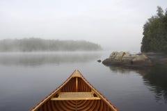 Pilbåge av en Cedar Canoe på en Misty Lake Royaltyfri Fotografi