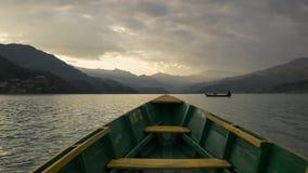 Pilbåge av en fartygsimning i en solnedgångsjö arkivfilmer