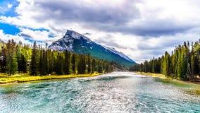 Pilbågefloden med mörker fördunklar att hänga över monteringen Rundle i den Banff nationalparken Royaltyfri Bild