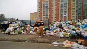 Pile énorme des déchets près des maisons photos stock