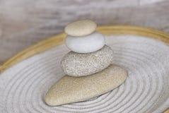 Pile équilibrée de caillou lisse dans une cuvette en bambou photographie stock libre de droits
