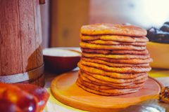 Pile of air pancakes on a wooden dinette, a traditional food family. pancakes of golden color Stock Photos