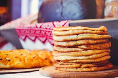Pile of air pancakes on a wooden dinette, a traditional food family. golden pancakes, pies in the background Stock Photos