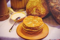 Pile of air pancakes on a wooden dinette, a traditional food family. pancakes of golden color, sour cream in the background Royalty Free Stock Photography