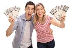 Pile allegre della tenuta delle coppie di soldi Fotografia Stock