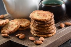 Pile of almond cookies, raw almonds and black tea on oak board. Closeup Stock Photography