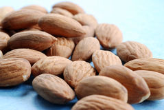 A pile of almonds. Against a blue background Royalty Free Stock Images