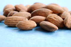 A pile of almonds #3. A pile of almonds against a blue background Stock Image