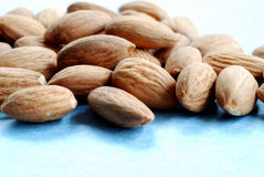 Pile of almonds against a blue Stock Image