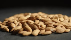 Pile of almonds on black background. 4K stock footage