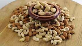 Pile of almonds, cashews and brazilian nuts spinning slowly and smoothly stock video