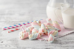 Pile of american twisted marshmallow on table with glass of milk Royalty Free Stock Photo