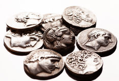Pile of ancient greek coins on reflective surface Royalty Free Stock Photography