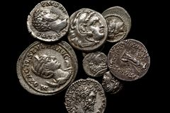 Pile of ancient silver coins on black background, top view royalty free stock photography