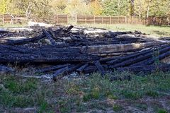 A pile of ashes and scorched planks on the site of a house fire Royalty Free Stock Photos