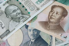 Pile of asian leading countries new emerging market money banknotes, indian rupee, chinese yuan and japanese yen, searching for y. Ield in alternative market stock image
