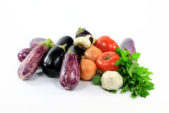 Pile assorted Eggplants and vegetables on white. Royalty Free Stock Image