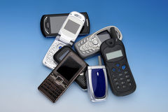 Pile of Assorted Mobile Phones. Assortment of mobile phones in a pile on blue Royalty Free Stock Photos