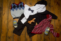 Pile of Baby boy outfit clothes on grunge wood background: onesie, sweater, trousers, shoes and toy Royalty Free Stock Photos