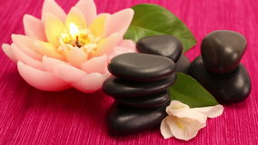 A pile of balanced black spa therapy stones. A pile of black spa therapy stones with lotus candle stock footage