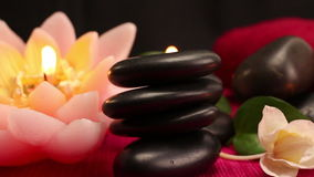 A pile of balanced black spa therapy stones. Surrounded by candles