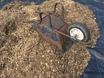 Pile of bark wood chippings. To be used as a weed suppressant with an upturned wheelbarrow resting on top stock image