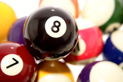 Pile of billiard balls. Close up of pile of billiard balls with focus on number eight ball stock image