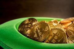 Pile of bitcoins inside green hat St Patricks Day. Treasure of golden bitcoins inside a green velvet hat on wooden table to celebrate luck on St Patrick`s Day of Stock Photography