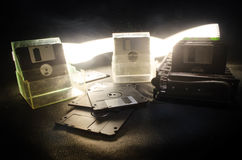 Pile of black floppy disks on dark background with light. Vintage computer attributes Stock Photography