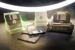 Pile of black floppy disks on dark background with light. Vintage computer attributes Royalty Free Stock Photography