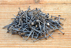 Pile of black mettalic nails. Pile of small black mettalic nails on wooden desk background Stock Photo