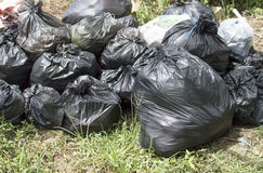 Pile of black plastic garbage bags on the ground Stock Image