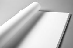 Pile of blank sheets of paper with curled upper page Stock Image