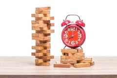 Pile of blocks wood game and red alarm clock on wooden table. St. Udio shot and isolated on white background Royalty Free Stock Photo