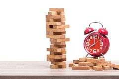 Pile of blocks wood game and red alarm clock on wooden table. St. Udio shot and isolated on white background Royalty Free Stock Photos