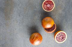 Top view of sicilian fruits.Whole and halves blood oranges on dark surface royalty free stock photography