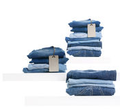 Pile of blue jeans with tag label on white shelf Royalty Free Stock Photo