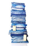 Pile of blue jeans with tags. Isolated on white Royalty Free Stock Photography