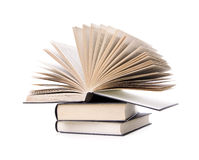 Pile of books. With one book open on white background Stock Photos