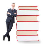 Pile of books. And a businessman leaning next to them Royalty Free Stock Photo